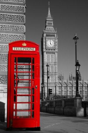 Photo pour Téléphone de Westminster boîte en couleur avec le Palais de westminster, en noir et blanc en arrière-plan. - image libre de droit