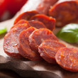 Spanish chorizo sausage with basil on chopping boa...