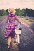 Woman with retro bicycle in lavender field