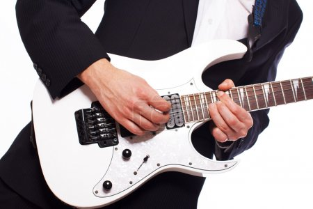 Portrait of handsome man posing on white background with guitar