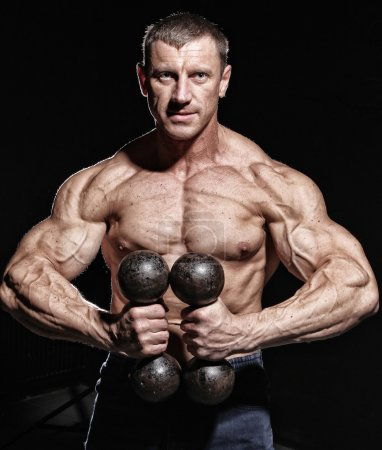 Photo for Man is having a photosession during his training with a pair of dumbbells - Royalty Free Image