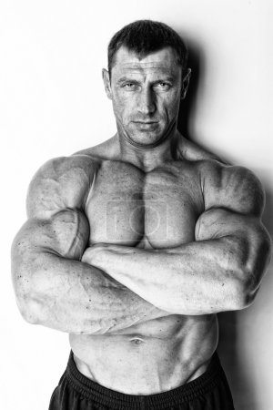 Well trained serious muscle man is posing with crossed hands