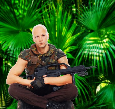 Photo for Image of armed soldier who is sitting in jungles - Royalty Free Image