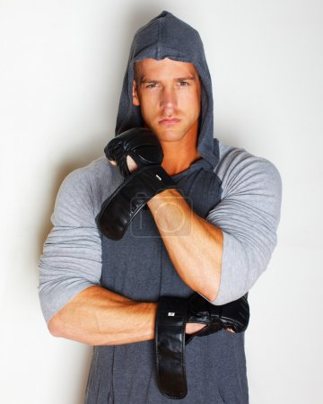 Attractive young sportsman in black gloves
