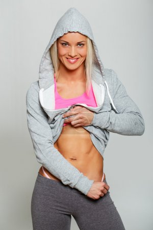 Smiling woman is demonstrating her trained body