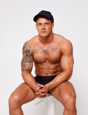Self confident topless bodybuilder on the chair