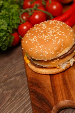 Wooden cutting board with vegetables and a Big Mac...