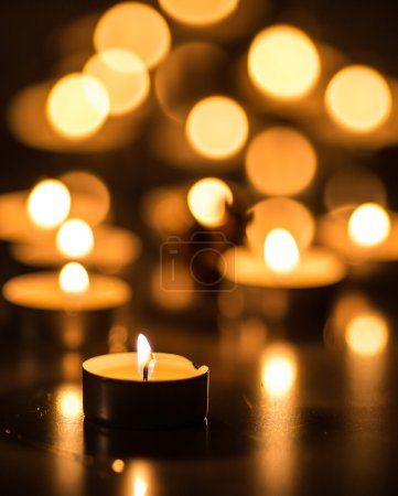 Single candle and many candles with bokeh effect