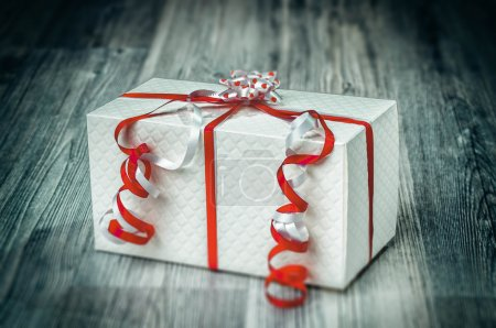 Textured white giftbox with pretty red ribbons