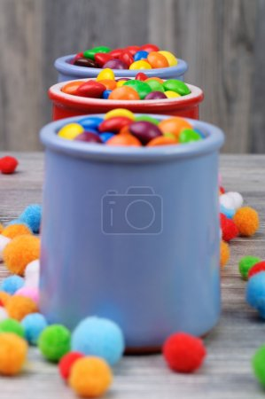 Three jars of colorful candies on a wooden background