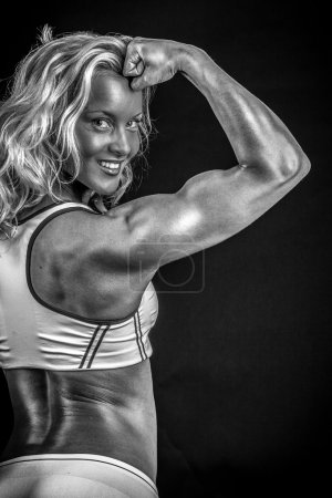 Monochrome photo of an athlete demonstrating her biceps