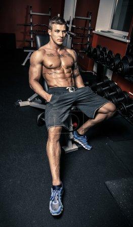 Bodybuilder in a fitness gym sitting