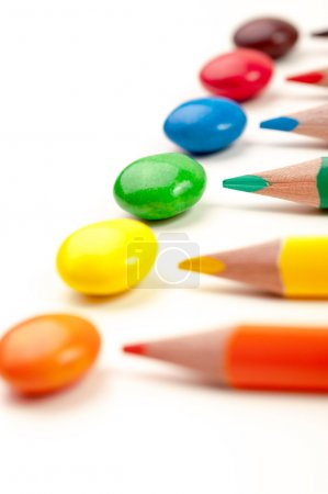 Photo for Rainbow color candies and same color pencils - Royalty Free Image