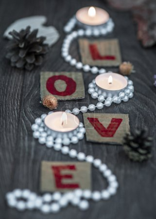 Pearl beads around three candles and letters L O V E