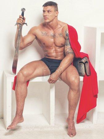 Photo pour Image de guerrier en manteau rouge assis en studio - image libre de droit