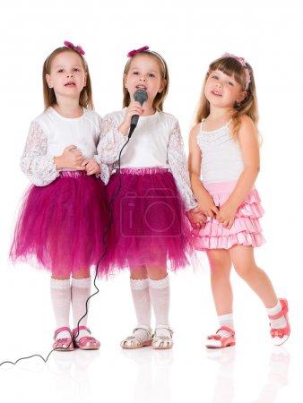Photo pour Adorables petites filles avec microphone, isolées sur fond blanc - image libre de droit