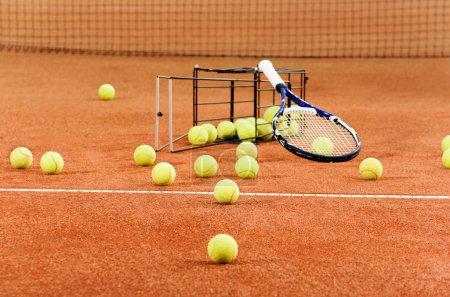 Photo pour Balles de tennis dispersés du panier sur Cour - image libre de droit