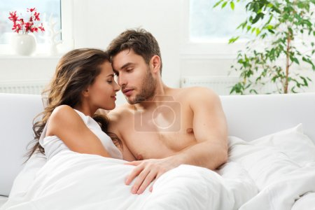Photo for Young adult heterosexual couple lying on bed in bedroom - Royalty Free Image