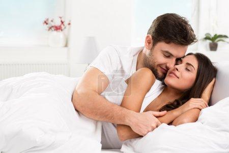 Photo pour Jeune adulte couple hétérosexuel couché sur le lit dans la chambre - image libre de droit