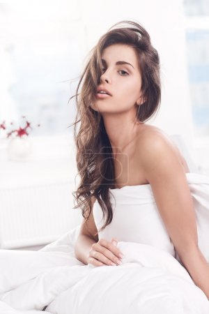 Photo for Young beautiful girl woke up and sitting on a bed - Royalty Free Image