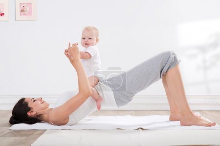Photo for Young mother does physical fitness exercises together with her baby - Royalty Free Image