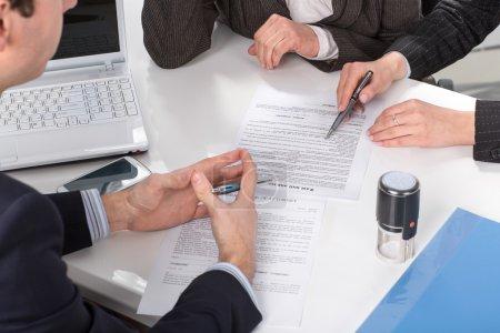 Photo pour Trois personnes assises à une table de signature de documents, gros plan de mains - image libre de droit
