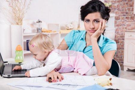 Photo pour Jeune femme d'affaires avec ordinateur portable et son bébé fille - image libre de droit