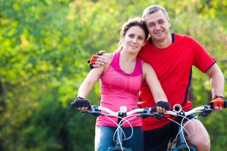 Photo pour Heureux couple d'âge mûr en vélo dans le parc vert - image libre de droit