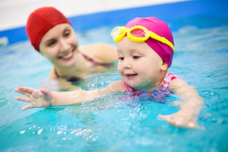 Photo for One year baby girl at his first swimming lesson wiht mother - Royalty Free Image