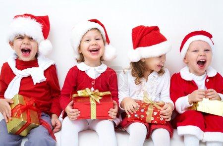 Photo pour Groupe de quatre enfants en chapeau de Noël avec cadeaux - image libre de droit