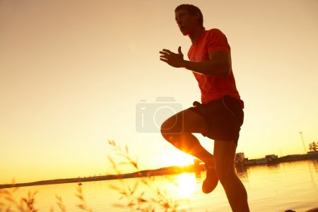 Photo for Young man running along the seashore at sunset - Royalty Free Image