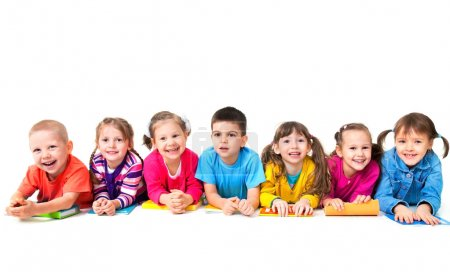 Photo for Group of seven children are lying on floor with copybooks together - Royalty Free Image