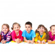 Group of seven children are lying on floor with co...