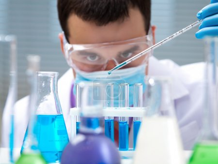 Photo for Investigator checking test tubes. Man wears protective goggles - Royalty Free Image
