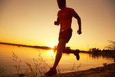 Mladý muž běží podél pobřeží při západu slunce