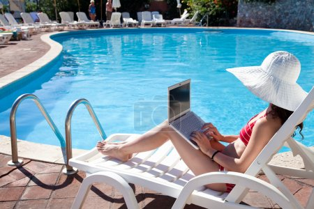 Young woman in big hat relaxing near the pool with...