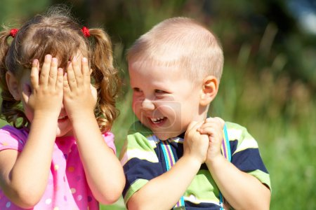 Photo for Two funny kids are playing, covering his face with his hands - Royalty Free Image