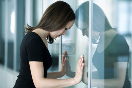 Young woman woman leaned against glass wall in cri...