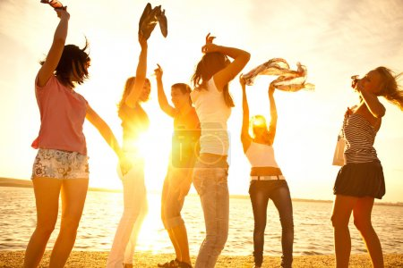 Photo for Happy young teens dancing at the beach on beautiful summer sunset - Royalty Free Image