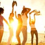 Happy young teens dancing at the beach on beautifu...