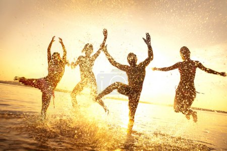 Photo for Group of happy young dancing and spraying at the beach on beautiful summer sunset - Royalty Free Image