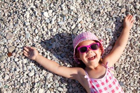 Photo pour Petite fille couchée sur une plage de galets - image libre de droit