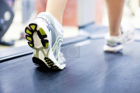 Photo for Woman's muscular legs on treadmill, closeup - Royalty Free Image