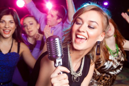 Photo for Young girl singing into microphone at party - Royalty Free Image