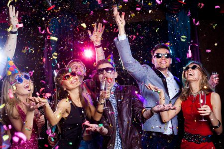 Photo for Cheerful young showered with confetti on a club party. - Royalty Free Image