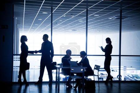 Photo pour Plusieurs silhouettes d'hommes d'affaires en interaction avec le centre d'affaires de fond - image libre de droit