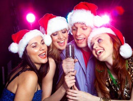 Photo pour Jeunes amis, déguisés en père Noël chantant dans microphone - image libre de droit