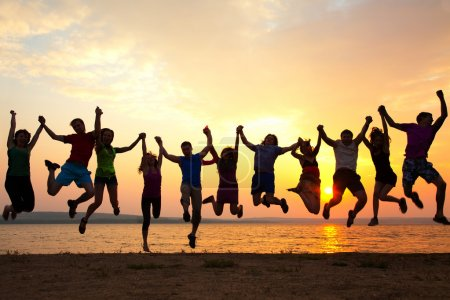 Photo for Group of happy young people jumping at the beach on  beautiful summer sunset - Royalty Free Image