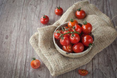 Photo for Cup with a bunch of fresh tomatoes on a wooden table - Royalty Free Image