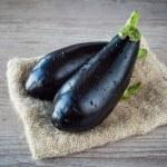 Assortment of fresh eggplant on wooden background...